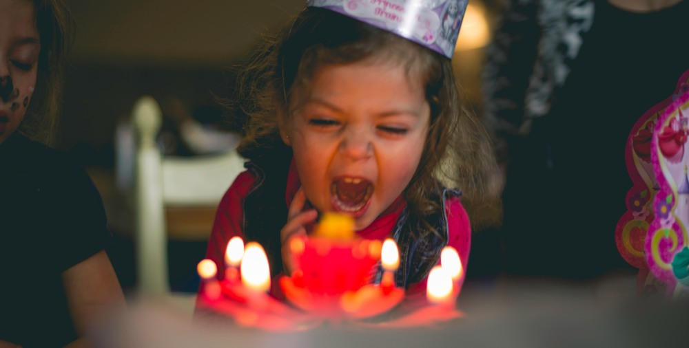 child blowing candles out