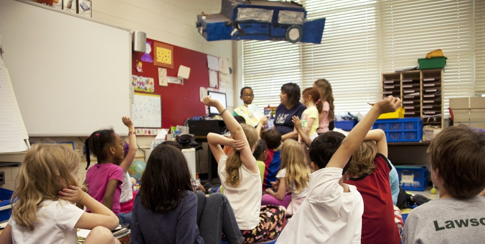 children with hands raised in classroom