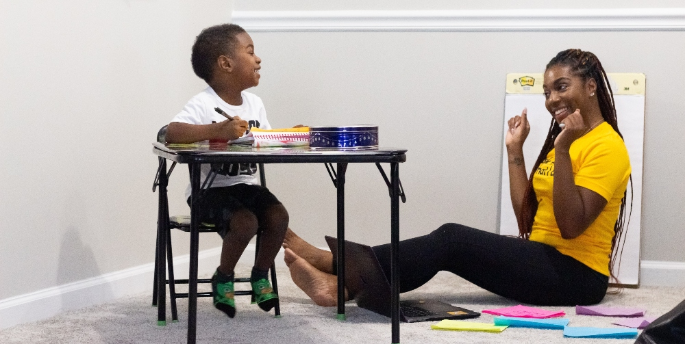 nursery practitioner sitting with child
