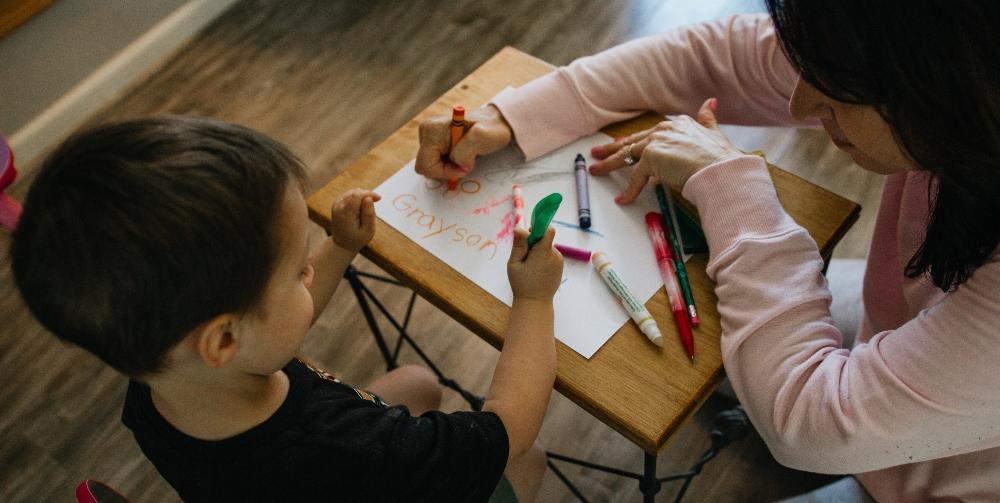 Nursery school teacher and child drawing
