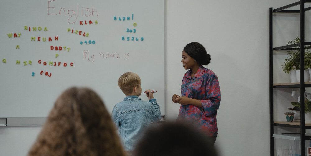 teacher observing child writing on a whiteboard