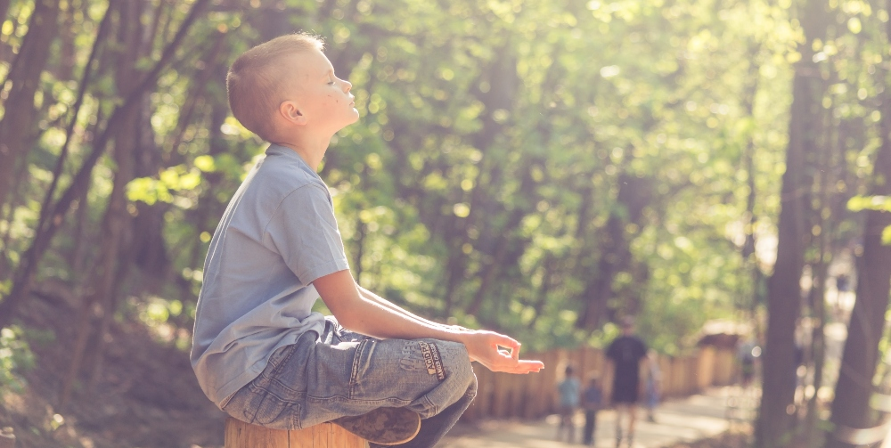 child meditating in a forest
