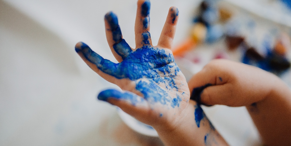 child with paint on their hand