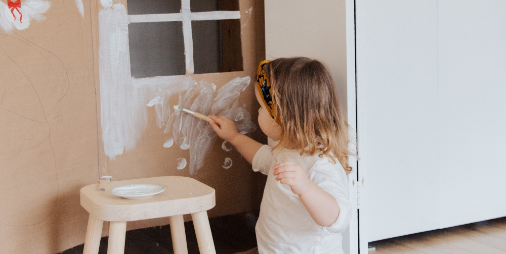 child painting a playhouse