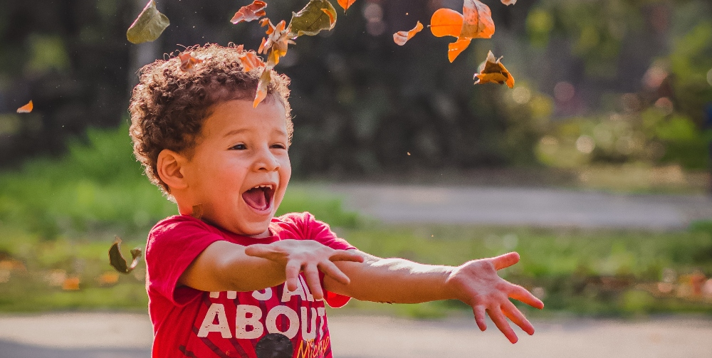 child laughing playing with leaves