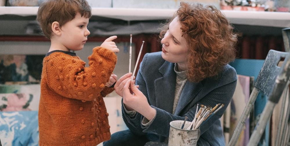 teacher showing child paintbrushes