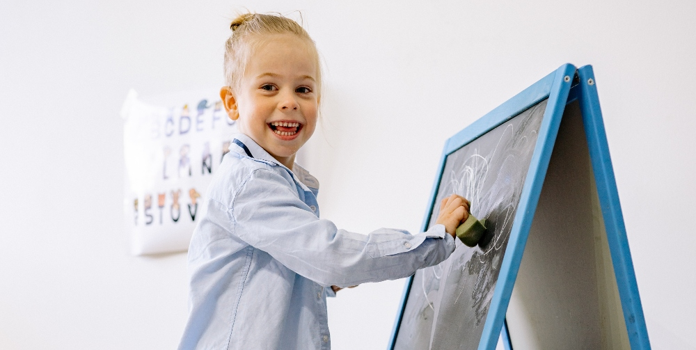 child standing at the front of the class