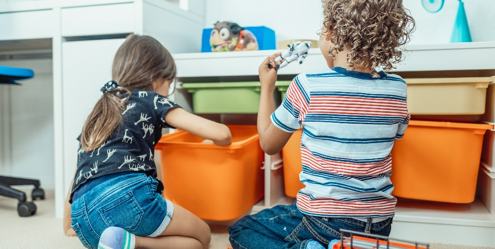 two children sitting looking at a playbox