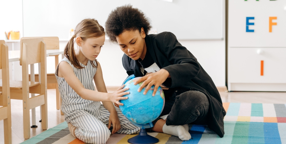 teacher and child looking at a globe