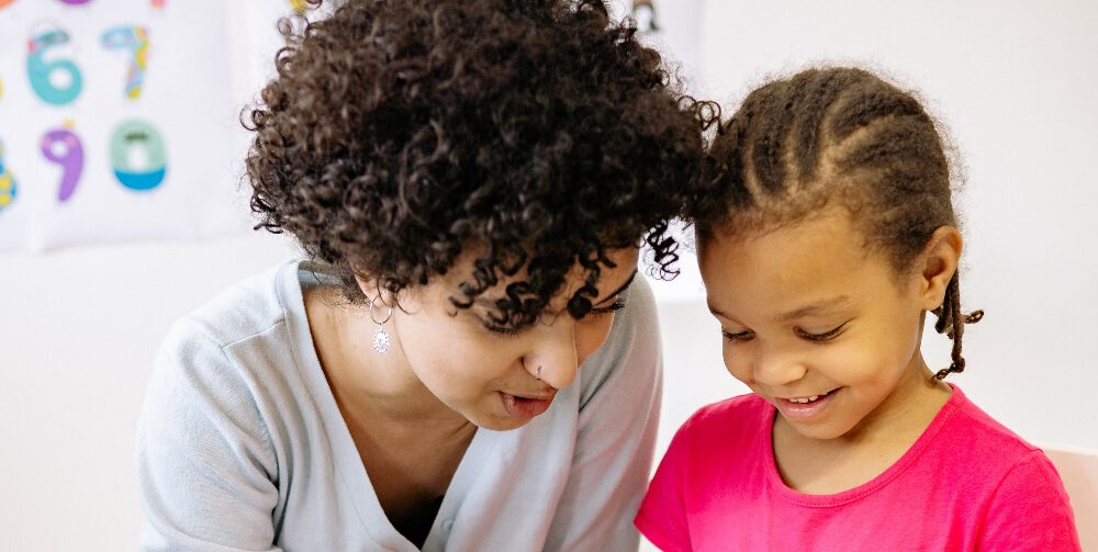 woman teaching a little girl